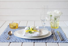 Table setting with blue checkered tablecloth, white napkin and y Royalty Free Stock Photography
