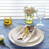 Table setting with blue checkered tablecloth, white napkin and y Royalty Free Stock Image