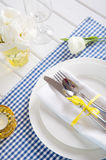 Table setting with blue checkered tablecloth, white napkin and y Royalty Free Stock Photo