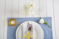 Table setting with blue checkered tablecloth, white napkin and y Stock Photography