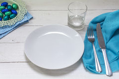 Table setting with blue and turquoise easter eggs, white plate, Royalty Free Stock Photo