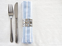 Table setting with blue an white striped napkin. On textured linen tablecloth with space for text Royalty Free Stock Images