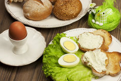 Table setting with Boiled eggs and bread with  cheese cream and easter decorations Stock Photos
