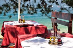 Table setting with bottles of olive oil and vinegar at tropical beach restaurant Stock Photo