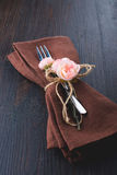 Table setting with brown napkin and rose. Royalty Free Stock Images