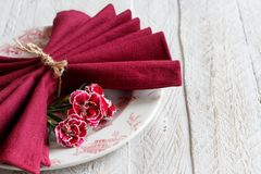 Table setting with carnation flowers. And dark red napkin Royalty Free Stock Photos