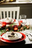 Table setting for celebration Christmas and New Year Holidays. Festive table in classic red and green at home with rustic details. Table setting for celebration Stock Photo