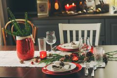 Table setting for celebration Christmas and New Year Holidays. Festive traditional red and green table at home. With rustic details Stock Photo
