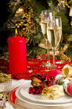 Table setting  for Christmas meal. Place setting for Christmas dinner with presents, plates, cutlery, serviette, candles,wine glasses, and a decorated tree Royalty Free Stock Photo