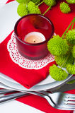 Table setting with chrysanthemums. Festive table setting with chrysanthemums, glasses, candles, napkins and cutlery in red and green colors Stock Photography