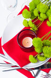 Table setting with chrysanthemums. Festive table setting with chrysanthemums, glasses, candles, napkins and cutlery in red and green colors Royalty Free Stock Images