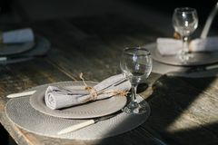 Table setting. Couple empty grey plates. Knife and fork. Old fashioned wine glasses. Rustic napkin. Wooden table. Selective focus Royalty Free Stock Photography
