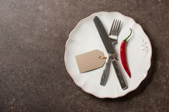 Table setting with cutlery, chili pepper and paper tag. Copy space Stock Images