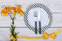 Table setting decorated with yellow lily with a ribbon. Royalty Free Stock Photos