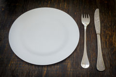 Table setting. Dinner plate, fork, knife. Table setting. A white plate with crossed silver knife and fork. Isolated on wood background royalty free stock images