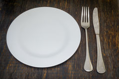 Table setting. Dinner plate, fork and knife. Table setting. A white plate with crossed silver knife and fork. Isolated on wood background royalty free stock photography