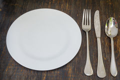 Table setting. Dinner plate, fork, spoon and knife. Table setting. A white plate with crossed silver knife and fork. Isolated on wood background stock images