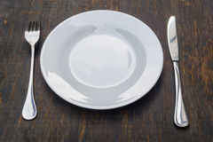 Table setting. Dinner plate, knife, fork. Table setting. A white plate with crossed silver knife and fork. Isolated on wood background stock images