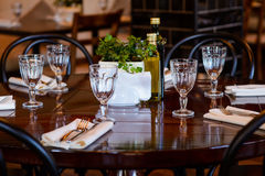Table setting before dinner at the restaurant. Round wooden table and chairs around it. On the table, forks, knives, napkins, olive oil and vinegar, vase with royalty free stock image