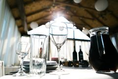 Table setting for dinner in restaurant, served wedding table with decor as candles, wine glasses, paper lanterns, wine. Bottles, water Stock Photo