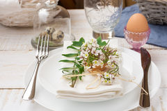 Table setting for Easter, white plates, napkin, bouquet of flowers, green leaves, quail eggs, outdoors, kinfolk royalty free stock images