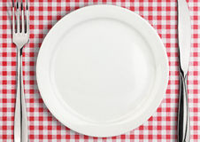Table setting, empty plate and silverware on red towel, top view Royalty Free Stock Image