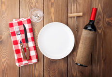 Table setting with empty plate, wine glass and red wine bottle Royalty Free Stock Image