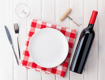 Table setting with empty plate, wine glass and red wine bottle Stock Photo