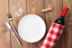 Table setting with empty plate, wine glass and red wine bottle. Top view over rustic wooden table background stock photo
