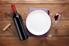 Table setting with empty plate, wine glass and red wine bottle Royalty Free Stock Photo