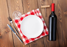 Table setting with empty plate, wine glass and red wine bottle Royalty Free Stock Photography