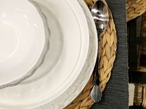Table setting of an empty white plate with silverware spoon Royalty Free Stock Photos