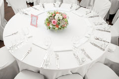 Table setting, festive round tables ready for guests. Beautifully organized event. floral arrangement in the center. fresh flowers cut-off Royalty Free Stock Images
