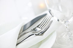 Table setting for fine dining. Elegant restaurant table setting for fine dining with plates cutlery and stemware Royalty Free Stock Images