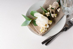 Table setting with floral decoration. Festive table setting with floral decoration, white roses, leaves and berries on a white corrugated background Royalty Free Stock Photo