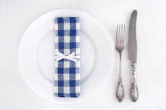 Table setting with fork, knife and blue checkered napkin Stock Photos
