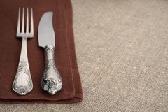 Table setting. Fork and knife on napkin with tablecloth and copyspace. Stock Images