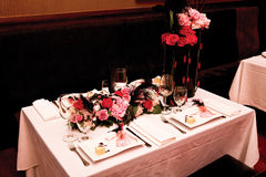 Table setting for four. A fancy table setting with flowers and pink tablecloth Royalty Free Stock Photography