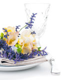 Table setting with freesias. Festive dining table setting with a bouquet of freesias flowers, crockery and cutlery, on white background, isolated Stock Photo