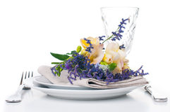 Table setting with freesias. Festive dining table setting with a bouquet of freesias flowers, crockery and cutlery, on white background, isolated Stock Photos
