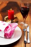 Table setting with a gift bag. Table setting with a pink polka-dot gift bag on white plate and candle in the background Stock Photos