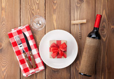 Table setting with gift box on plate, wine glass and red wine bo Stock Image
