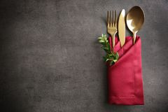 Table setting with golden cutlery in red napkin. On grunge background Stock Image