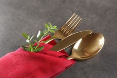 Table setting with golden cutlery in red napkin. On grunge background Royalty Free Stock Photo