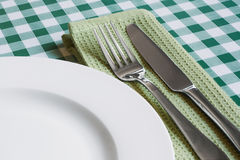 Table setting on green Gingham table cloth. Place setting with empty plate, knife and fork on a green gingham background popular symbol for diners and cafes Royalty Free Stock Photos