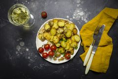 Fried potatoes with mushrooms, onion and cherry tomatoes in white plate at black background. royalty free stock images
