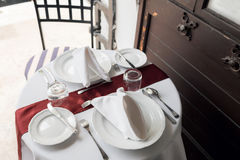 Table setting for a lovey dinner. Empty glasses set in restaurant. Part of interior. napkins, plates, and cutlery. Stock Images