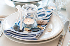 Table setting in maritime style. With candles, sea shells and striped napkins, close up Stock Photo