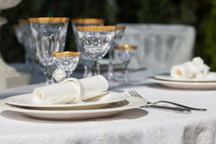 Table setting with napkin and win glasses. An elegant dining table setting with napkin and win glasses outdoors Stock Photography