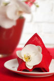 Table setting with orchid flowers. Table setting with white orchid flowers on red tablecloth royalty free stock images